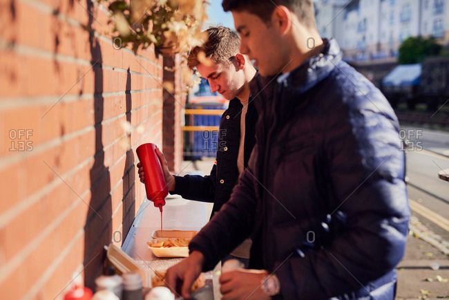 Two young men at takeaway food stand, pouring ketchup on food, Bristol, UK