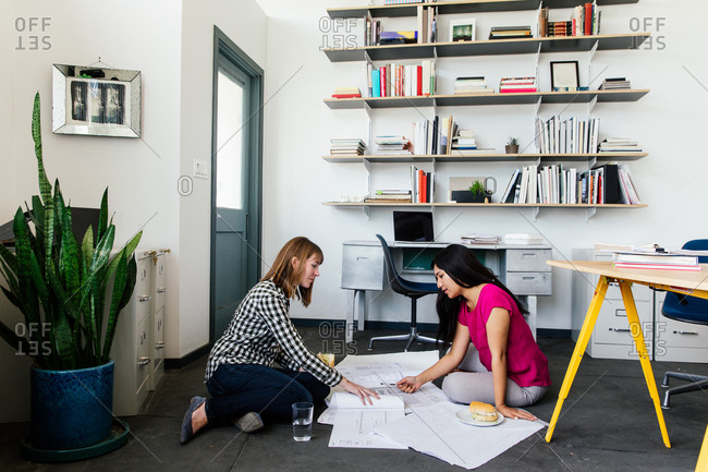 Colleagues on office floor looking at blueprints