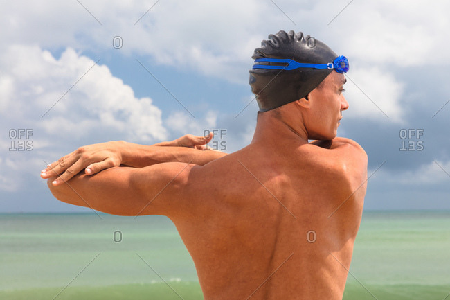 Rear view of muscular male swimmer on beach warming up