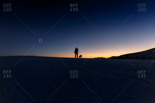 Silhouetted view of man and dog standing on hill horizon at night