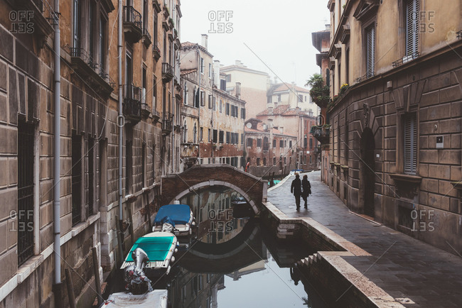 Rear view of couple strolling along canal waterfront, Venice, Italy
