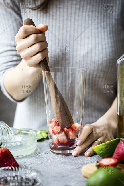 A woman is photographed as she is muddling strawberries to make margaritas.