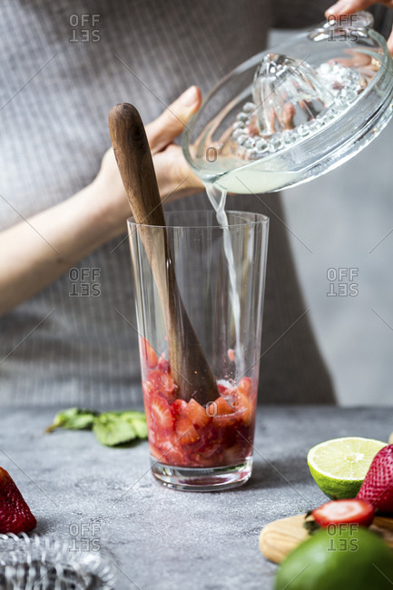 A woman is photographed as she is pouring lime juice into a glass to make margaritas.