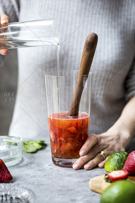 A woman is photographed as she is pouring syrup into a glass to make margaritas.
