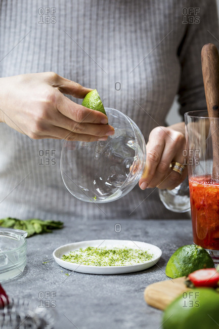 A woman is photographed as she is wetting the rim of a margarita glass with a lime wedge.