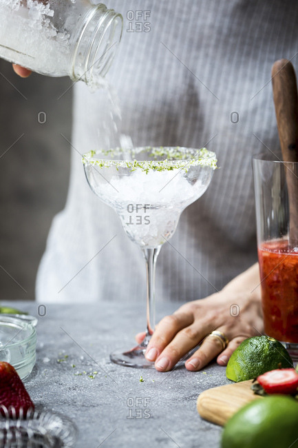 A woman is photographed as she is pouring ice into a margarita glass to make margaritas.