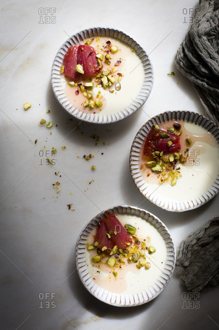 Classic vanilla pannacotta topped with roasted rhubarb and chopped pistachios in a ceramic tart pan on a marble table on top view