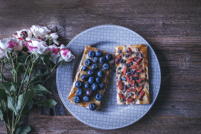Crispy rye bread toast with tahini and honey, topped with fresh blueberries, goji berries and cacao nibs