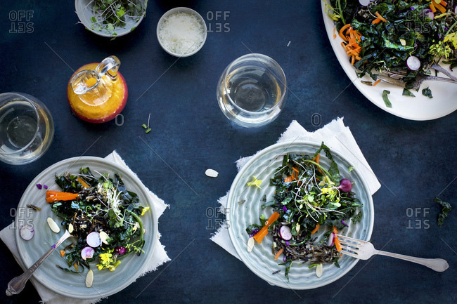 Kale Wild Rice Salad with Blood Orange Vinaigrette served with white wine. Photographed on a dark blue background.