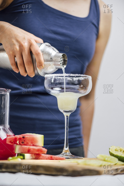 A woman pouring margarita from a shaker into a rimmed margarita glass photographed from front view. Watermelon slices and lime slices accompany.