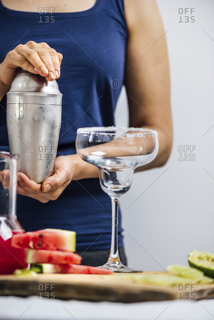 A woman preparing margarita using a shaker photographed from front view. An empty margarita glass, watermelon slices and lime slices accompany.