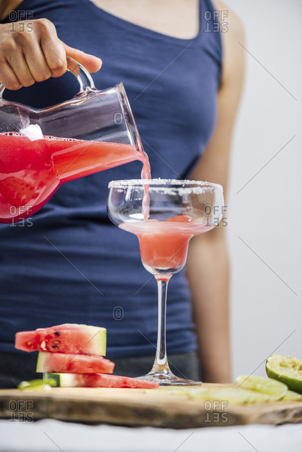 A woman pouring watermelon margarita fron a jug into a rimmed margarita glass. Watermelon slices and lime slices accompany.