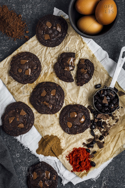 Mexican hot chocolate cookies on a piece of light brown paper photographed from top view with a cup of chocolate chips, eggs, cayenne pepper, cocoa powder and cinnamon.