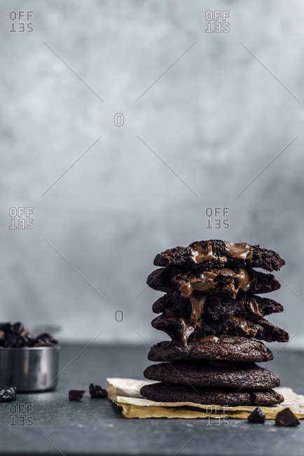 A stack of Mexican hot chocolate cookies photographed from front view. Chocolate chips in the cookies are melting. A cup of chocolate chips accompany.