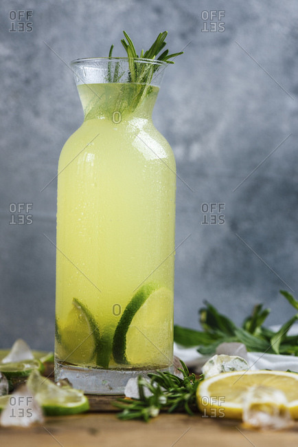 Lemonade flavored with mint and rosemary served in a bottle photographed on a wooden board with a grey background from front view. Lemon slices, lime slices and ice pieces accompany.