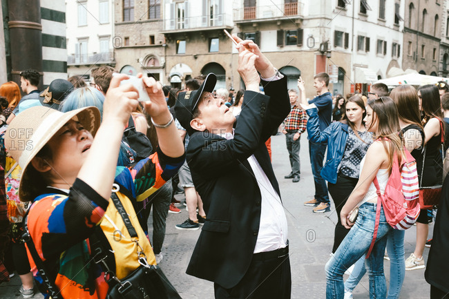 Florence, Italy - May 12, 2017: Tourist taking photos with phones