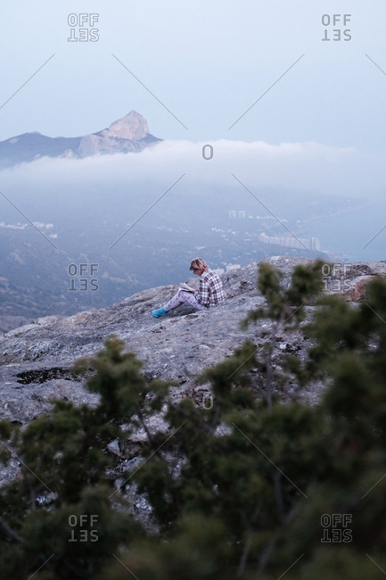 Woman on mountain with cloudy vista