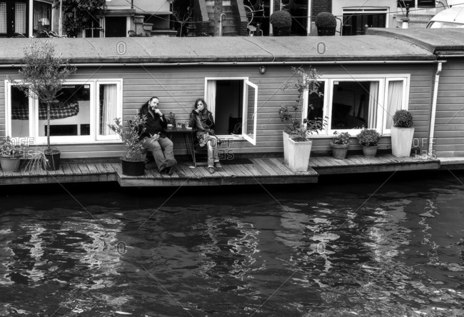 Amsterdam, Netherlands - June 18, 2016: Two people sitting on the porch of a house boat