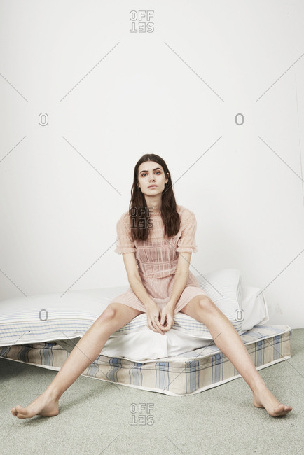 March 16, 2014: Woman in a pink ruffled dress sitting on a pile of mattresses