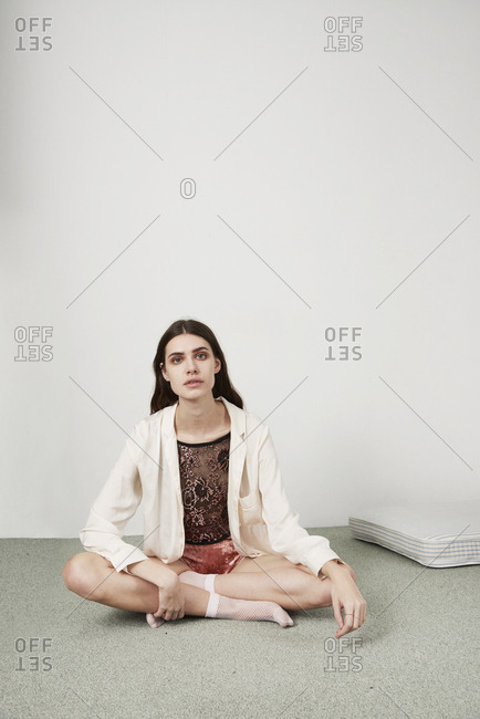 March 16, 2014: Fashion model in white shirt sitting cross-legged on floor