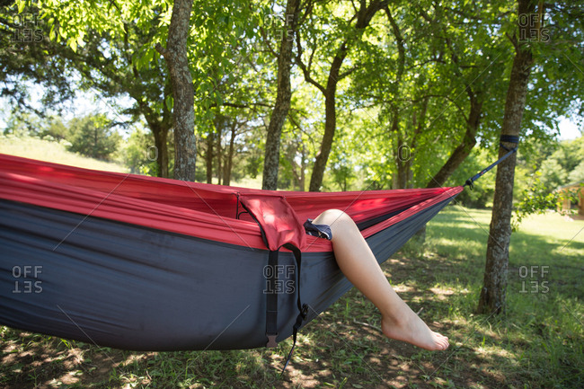 Leg of a boy hanging from a camping hammock in the forest