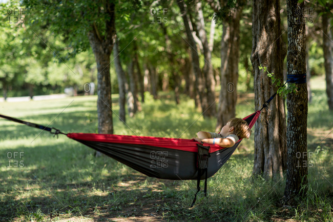 Boy napping in a camping hammock between trees