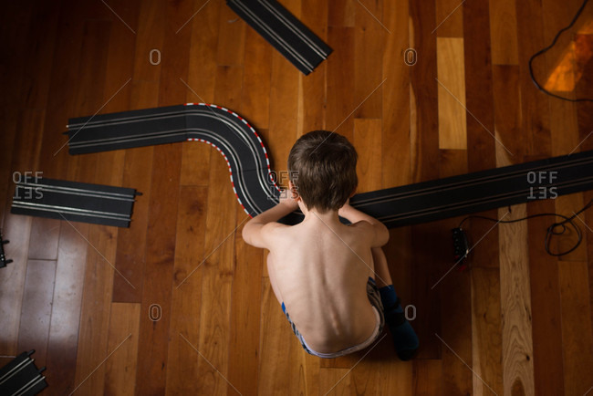Boy putting together toy race tracks on a wooden floor