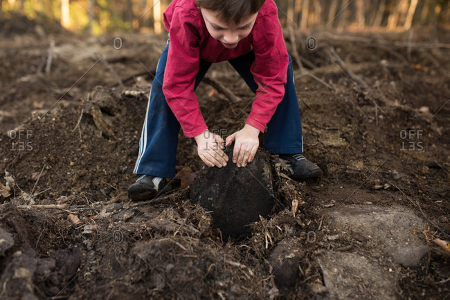 Boy digging up a large rock from the earth