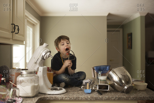 Boy sitting on a counter licking batter from the paddle of a mixer