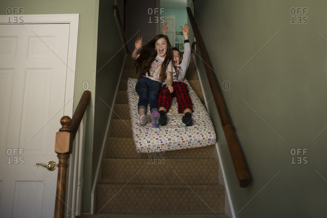 Sister and brother sliding down steps together on a mattress