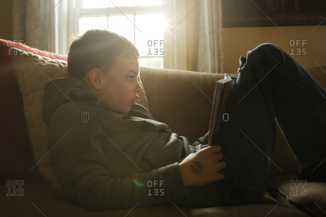 Boy curled up on a couch reading a book