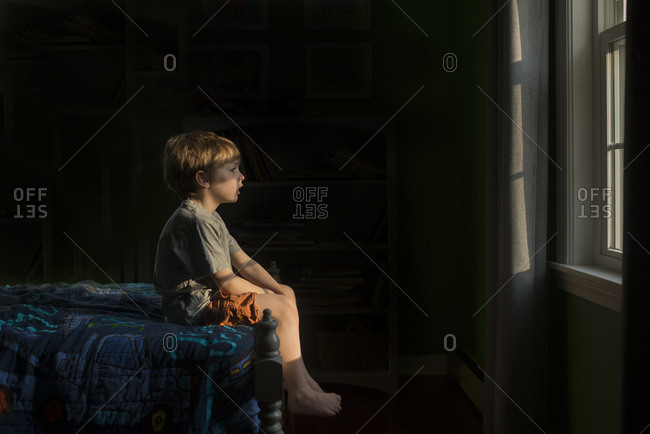 Boy sitting on the edge of his bed looking out of a window