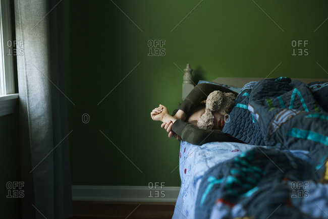 Boy sleeping in a bed with his teddy bear draped over his face