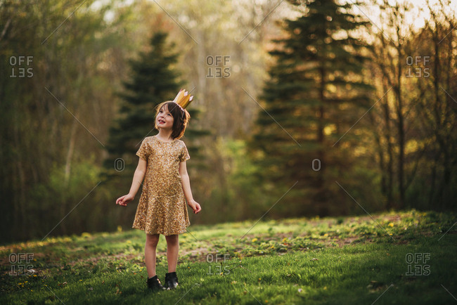 Young girl outside in fancy gold dress and crown