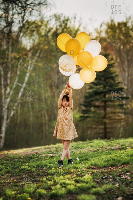 Young girl in gold dress with gold balloons