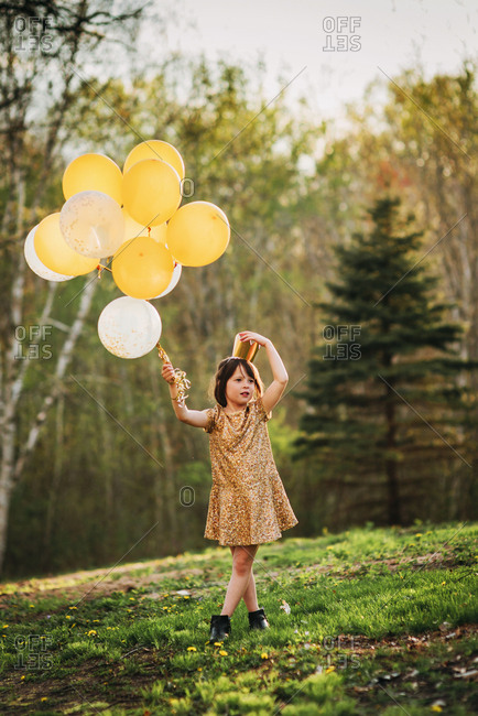 Young girl in gold dress with balloons