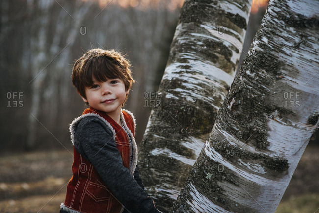 Young boy posing by large tree