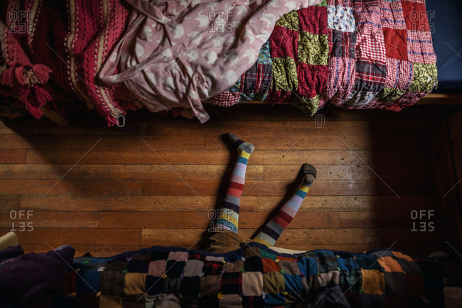 Overhead view of child's feet under a bed