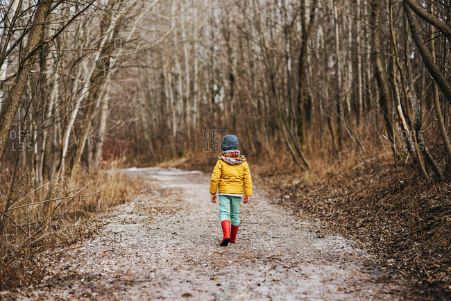 Young boy hiking on a trail in the winter