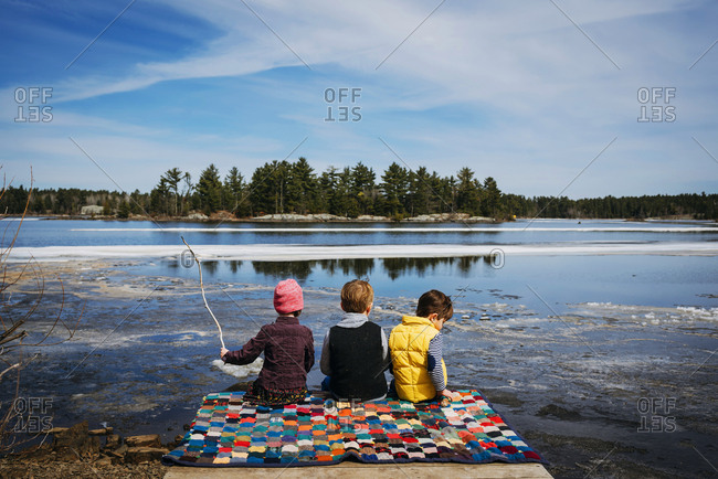 Three young children having a picnic on a dock by a frozen lake