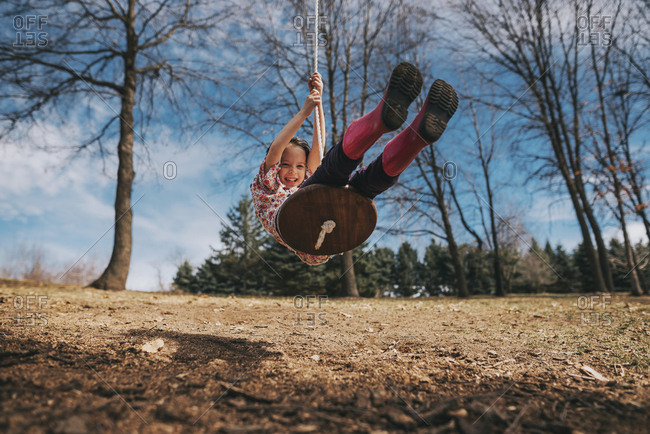 Young girl swinging on wood swing in backyard under trees and blue sky