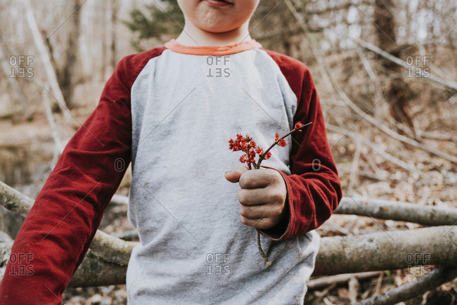 Young boy with dirty hands holding flower blossoms
