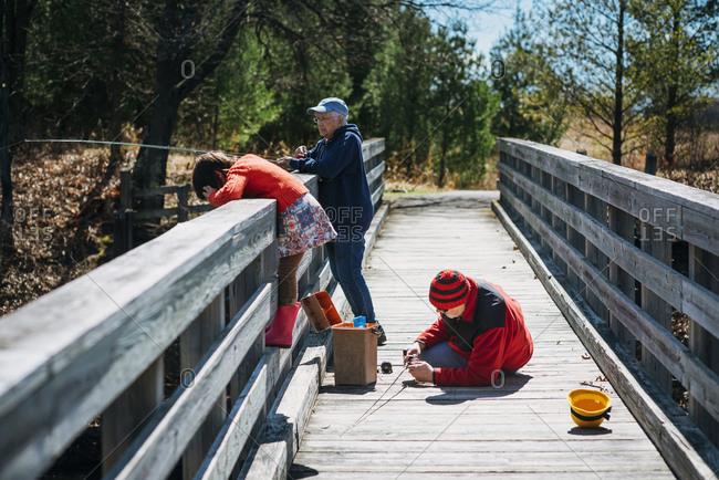 Grandmother and grandkids fishing off a  bridge