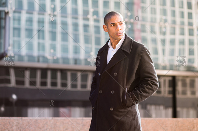 Cool young man wearing coat holding hands in pockets and looking away. Horizontal outdoors shot.