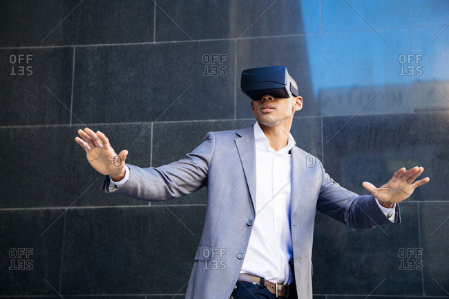 Man dressed in formal wear using the virtual reality headset. Horizontal outdoors shot.