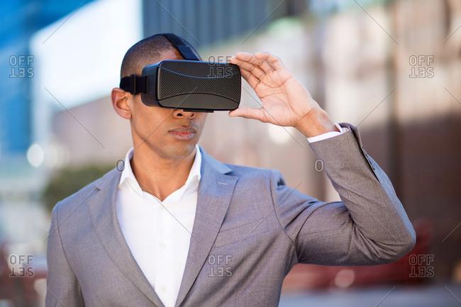 Horizontal shot of young man wearing suit adjusting the VR helmet.