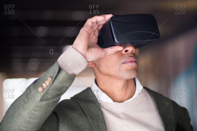 Confident businessman with VR goggles on his head.