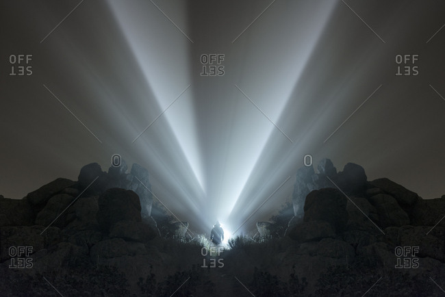 Man with flashlight at night in the mountains under a thick fog
