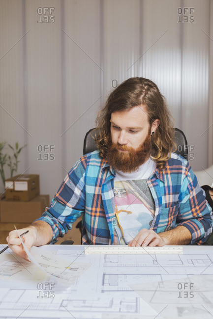 Young bearded architect in check shirt sitting at workplace and working on project in office.