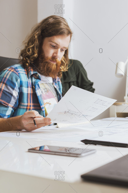Young bearded male in check shirt working with blueprint at workplace in office.